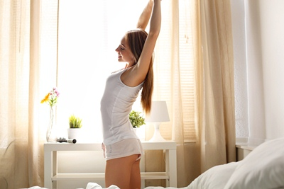 Beautiful smiling young long haired woman wake up early morning